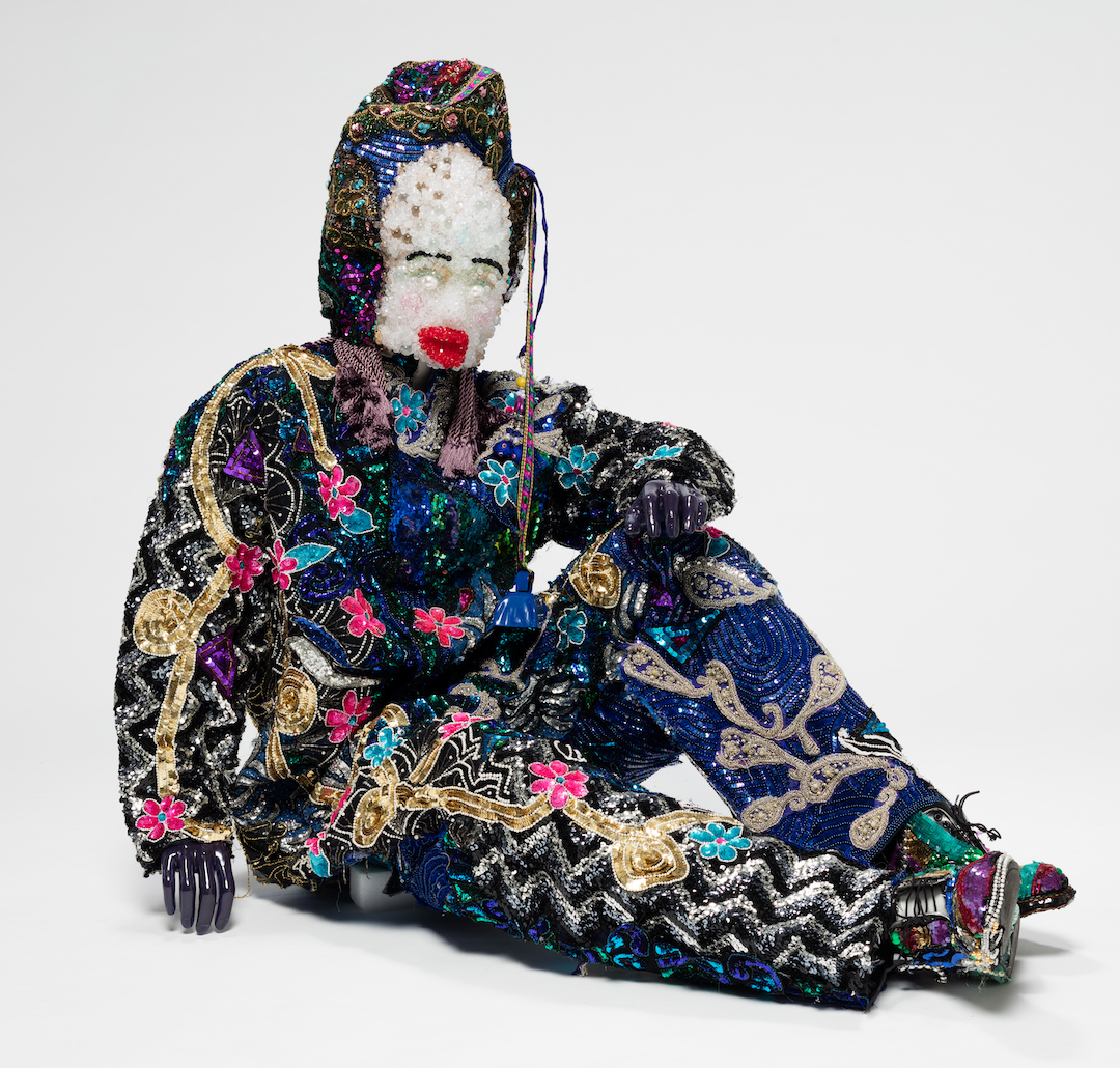 A reclining mannequin adorned with beads and colorful materials
