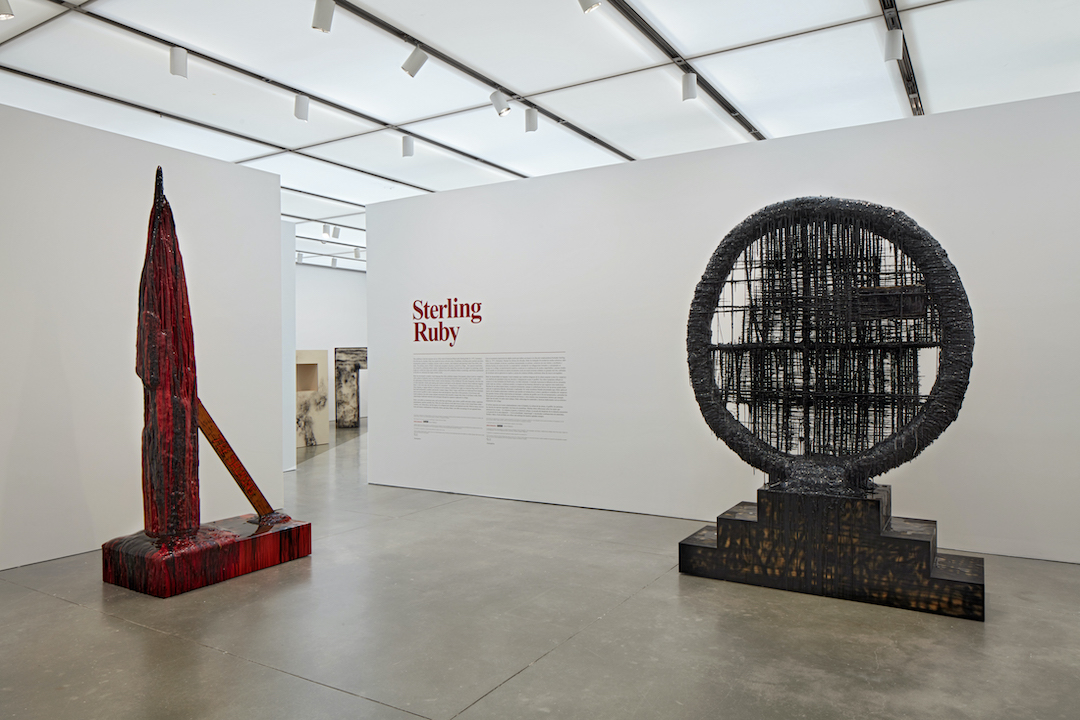 "Two monumental sculptures in a gallery with ""Sterling Ruby"" and exhibition text written on the wall"