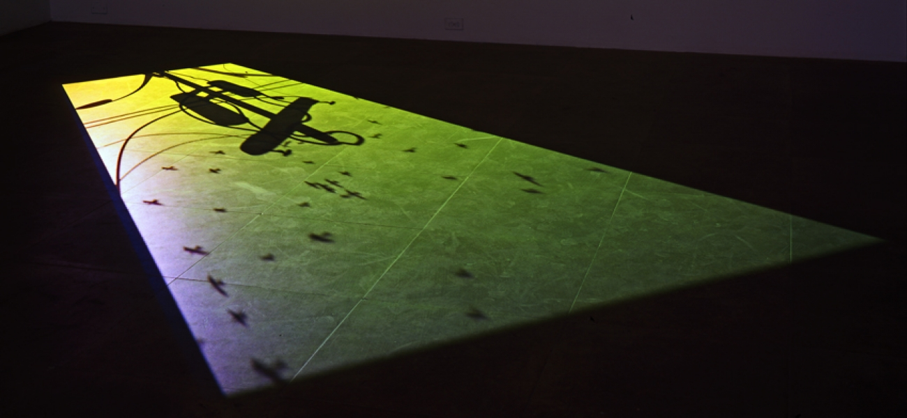 A video still of a green skyline with the silhouettes of flying birds and a telephone line projected onto the floor.