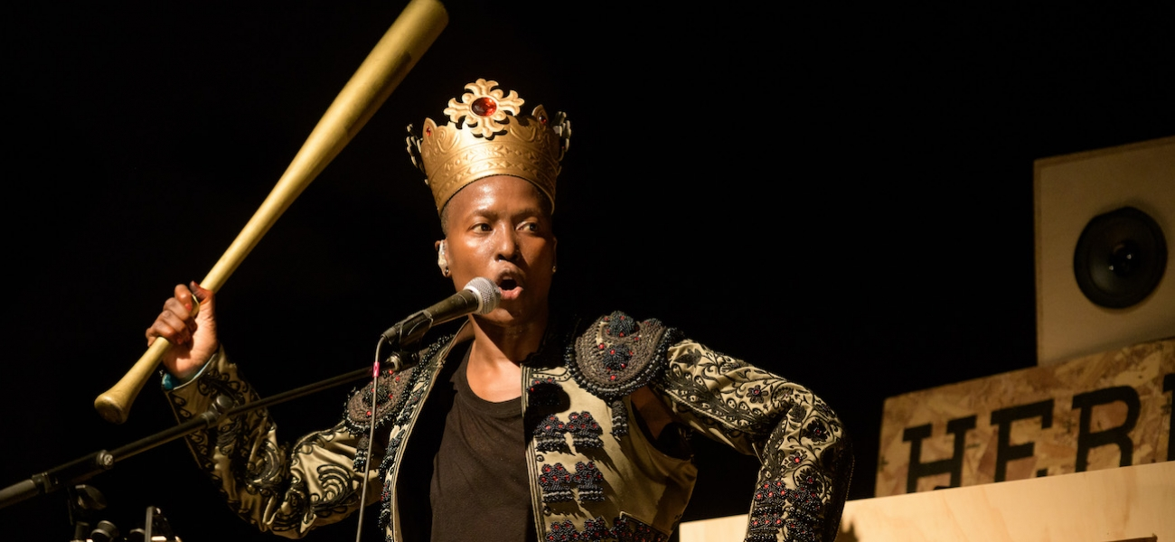 A dark-skinned woman wearing a crown holds up a baseball bat in one hand. She's on a stage set and speaking or singing into a microphone on a stand.