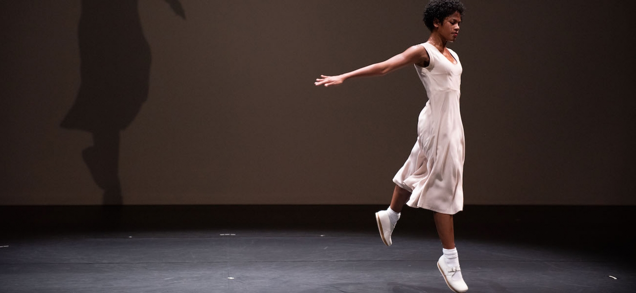 A dancer in a pale dress hops with arms stretched behind her on a dark stage.