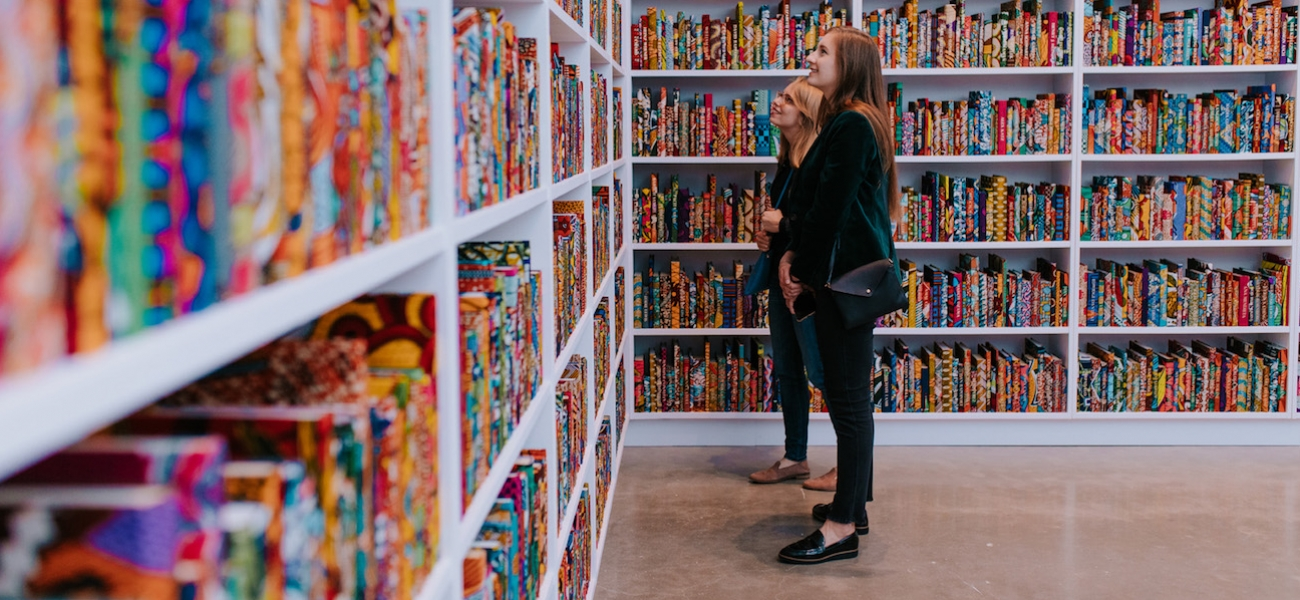 Two women look at walls of books covered in colorful dutch wax fabric, with names embossed in gold on the spines.