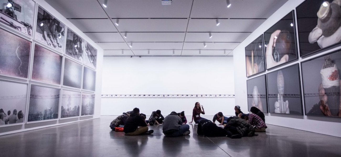 Students doing a writing exercise within the exhibition Walid Raad.