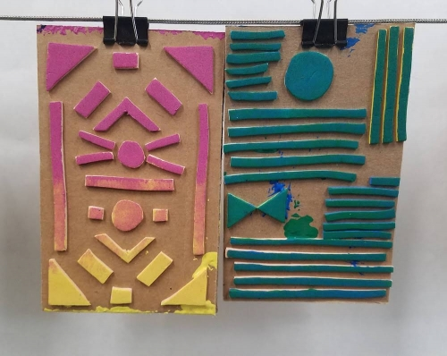 Two cardboard sheets with thick cut-out shapes glued to the surface.