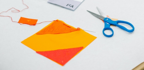 A piece of orange fabric square next to a pair of scissors on a table.