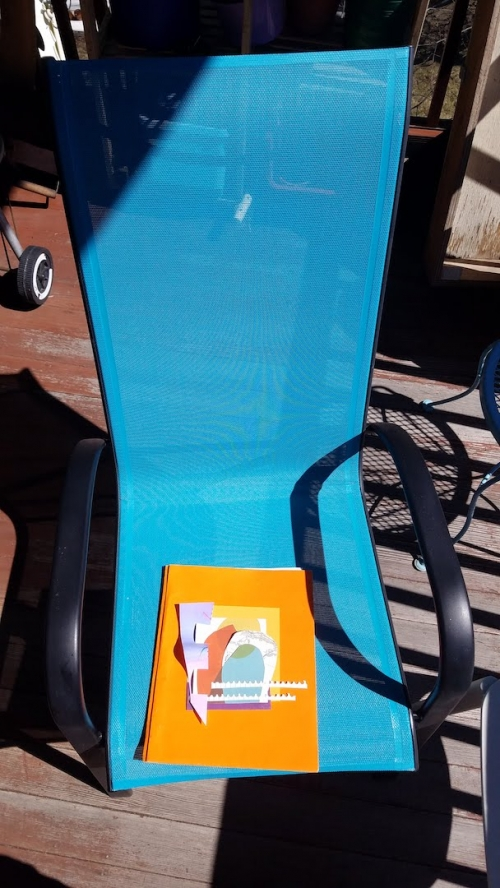 A decorated fabric quilt square sitting on a lawn chair outside on a porch.
