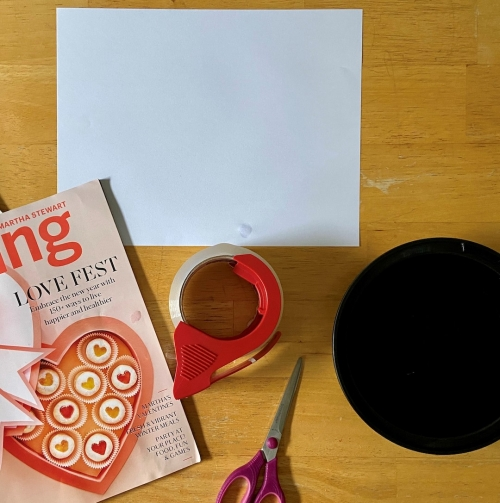 Art materials including clear packing tape, scissors, glossy magazine, white sheet of paper, and a black plastic bowl.