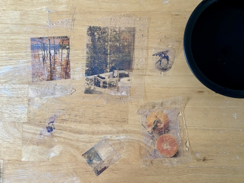 Various images and illustrations on clear tape, still slightly wet, after having been soaked in a bowl of water.
