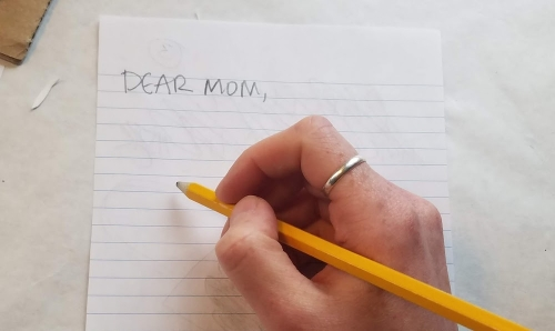 """A pencil in hand with the words """"Dear Mom"""" written on a single piece of notebook paper."""
