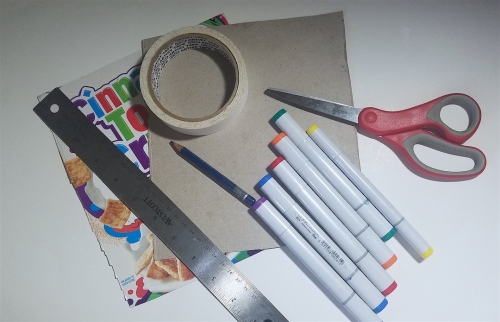 Scissors, markers, tape, a metal ruler, and the cut-out front and back of a cardboard cereal box.