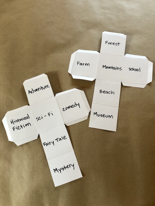 Two cut-out dice with writings of genres and settings on each side.