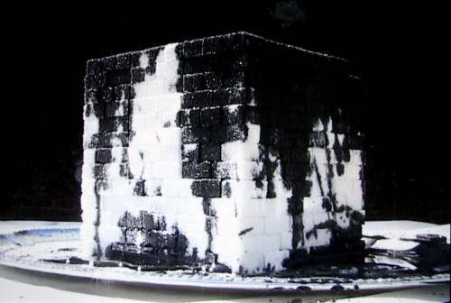 A video still of a stack of sugar cubes covered in dark oil on a silver plate.