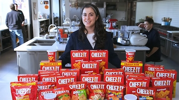 A woman standing behind dozens of boxes of Cheez-Its in a large commercial kitchen