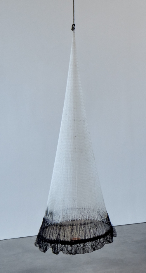 A conical hanging sculpture made from a fishing net that is white except for a dark bottom, the widest part.