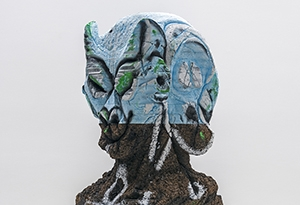 A bust by Huma Bhaba, that is gray and organic in texture, with the top covered in light blue paint.