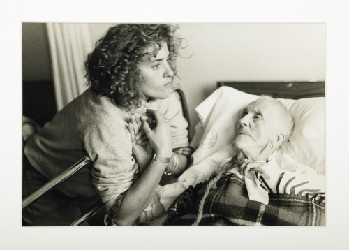 A black-and-white photograph of a light-skinned young woman leaning over the railing of a hospital bed, holding the hand of a frail and pale elderly woman who lays in the bed and looks up at her.