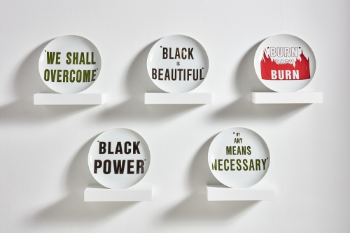 """An installation of five ceramic plates displayed on five shelves and printed with the sayings""""We Shall Overcome,"""", """"Black is Beautiful,"""", """"Burn Baby Burn,"""", """"Black Power,"""", and """"By Any Means Necessary."""""""