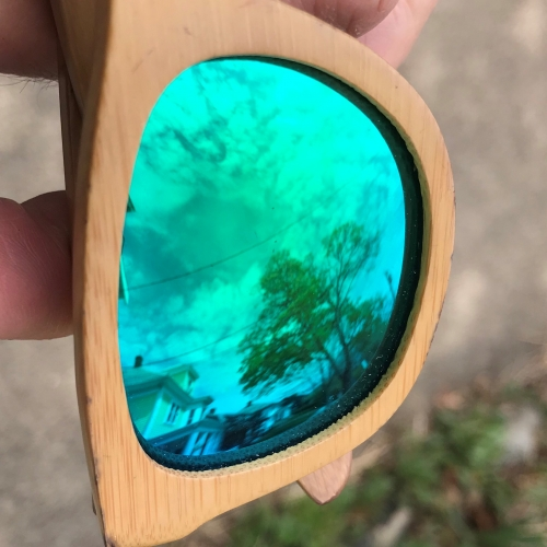A close-up, sideway view of one lens of a green-tinted sunglasses with wood frames.