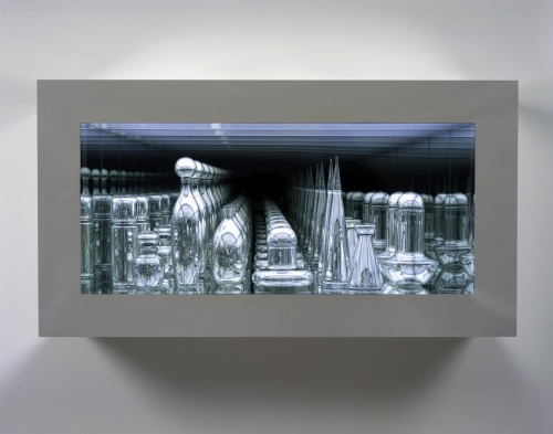 An installation of a mirrored glass case holdings hand-blown mirrored glass geometric objects to create an infinitely repeating mirrored visual effect.