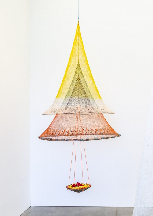 A hanging sculpture made of fishing nets suspended to create an inverse conical shape.