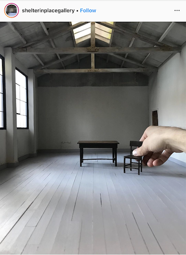 Instagram image of a hand placing miniature furniture in a realistic-looking gallery space