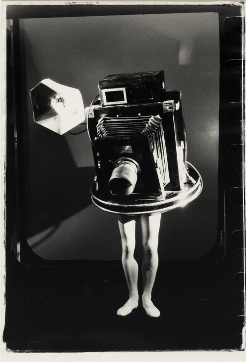 A black-and-white photograph of a person wearing a full-body costume of an antique press camera on a photo set with only their pale exposed legs visible.