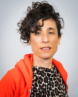 A headshot of choreographer Netta Yerushalmy. She has dark curly hair pulled back and an open orange hoodie over a leopard-print top.