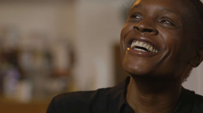 A film still shows an African American woman laughing.
