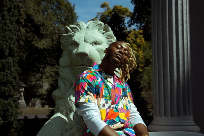 A photo portrait of Cliff Notez, an African-American musician in a colorful shirt leaning against a lion statue with a roman column and greenery in the background.