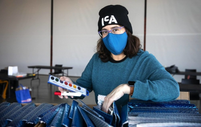A woman with pale skin, dark hair, a blue mask, and a hat with the ICA logo packs art supplies into shiny blue envelopes.