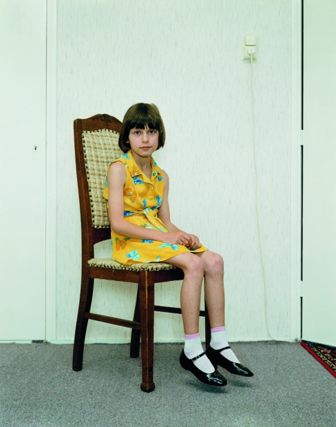 A color photograph of a light-skinned girl with short brown hair in a yellow dress, mary janes, and white socks sitting on a wooden chair, positioned at an angle and gazing at the viewer.