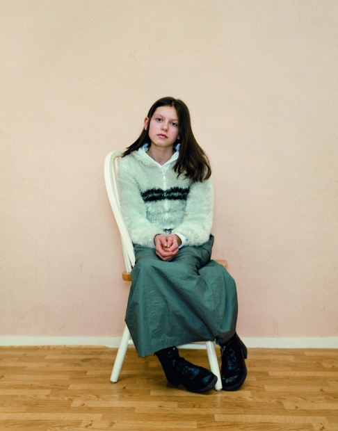 A color photograph of a light-skinned girl with long brown hair wearing a pale blouse and long green skirt sitting sideways on a chair to face the viewer.