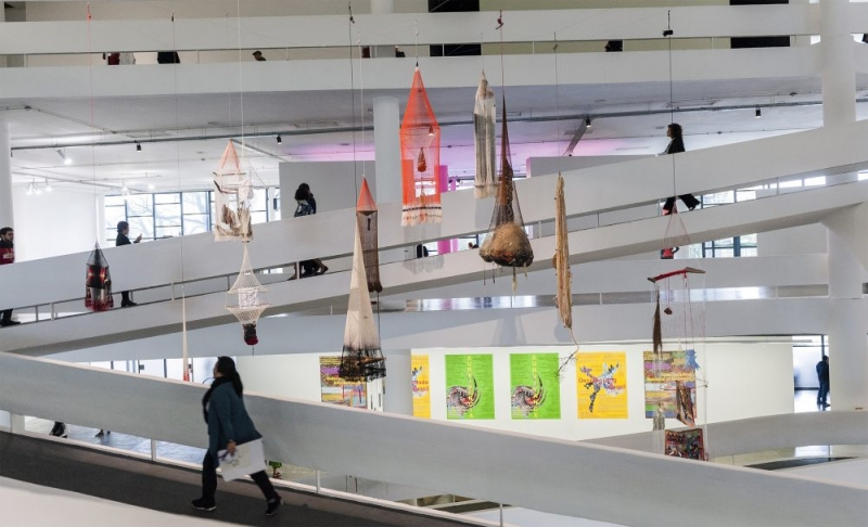 Objects handmade from fishing nets hang from the ceiling in an atrium with sloping floors