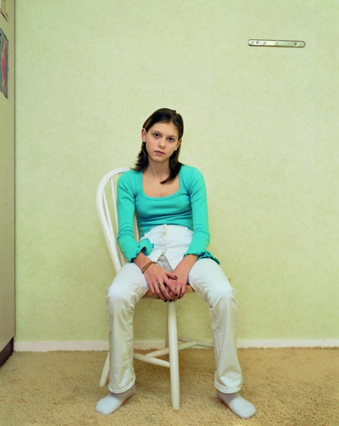 A color photograph of a light-skinned girl with long brown hair wearing a bright, turquoise blouse and white pants sitting slumped on a chair, facing the viewer.