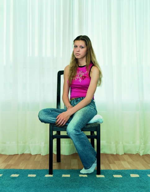 A color photograph of an light-skinned adolescent girl with blondish hair wearing a pink tank and blue jeans sitting on a chair, positioned at an angle and gazing at the viewer.