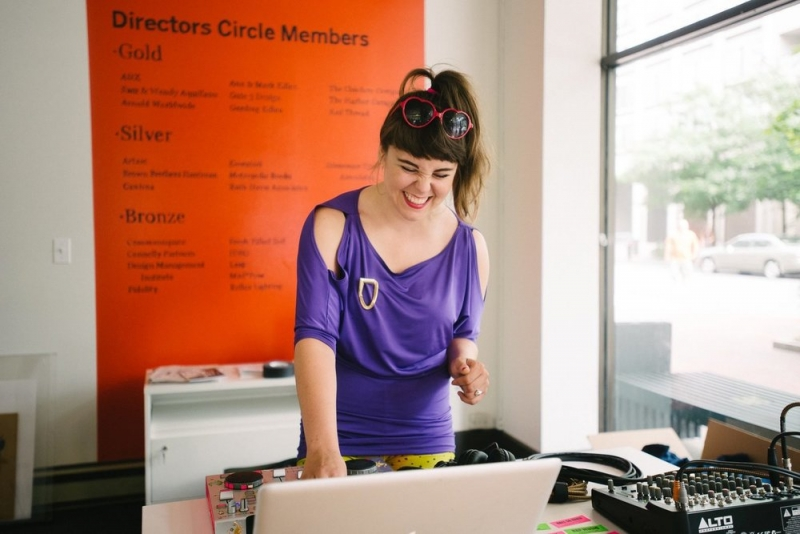A DJ smiling over her laptop and soundboard equipment in a sunny, well-lit venue.