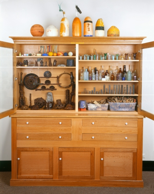 A sculpture of a large, wooden cabinet  with open glass doors displaying a variety of found objects including bottles and buoys.