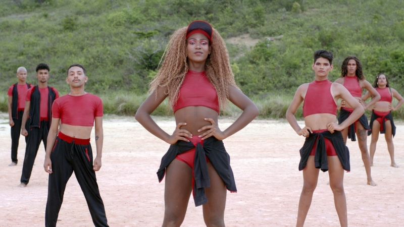 A video still depicts dancers of color standing in a V-formation in red and black costumes posing as they face the camera with confidence.