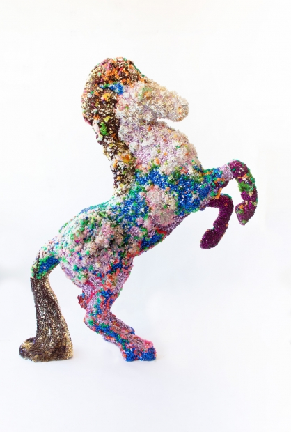 Sculpture of a horse rearing, encrusted with colorful beads, bells, sequins, and other homespun materials.
