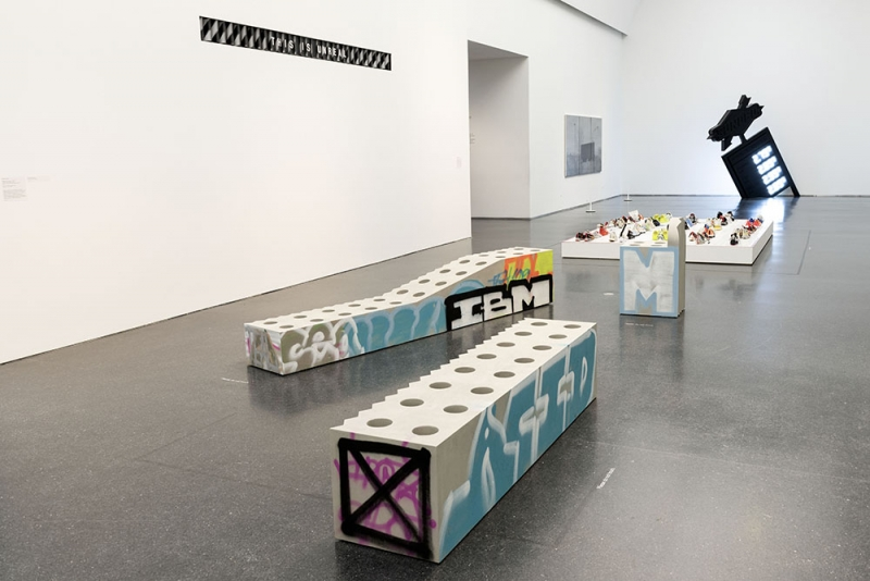 A white gallery with three concrete benches with graffiti on them.