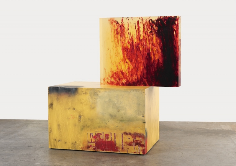 One three-dimensional oblong form sits stacked askew on top of another. The top for is translucent yellow with swirls of red that appear to be rising up. The bottom form appears to be a wooden box painted yellow, with the letters WS ROLLING hand-drawn on the side in red.
