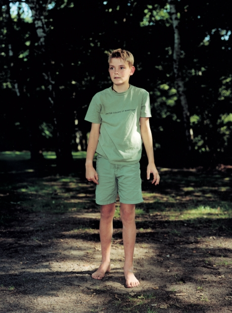 A color photograph of a light-skinned young boy in grayish-green standing in a wooded park.