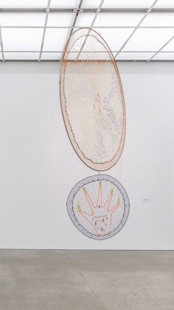 A hanging sculpture made of two fishing nets stretched around two metal rings with colorful, embroidered illustrations