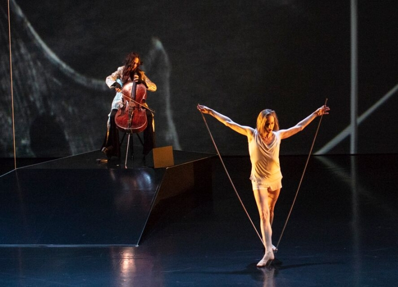 A dancer holding a long string and a cellist.
