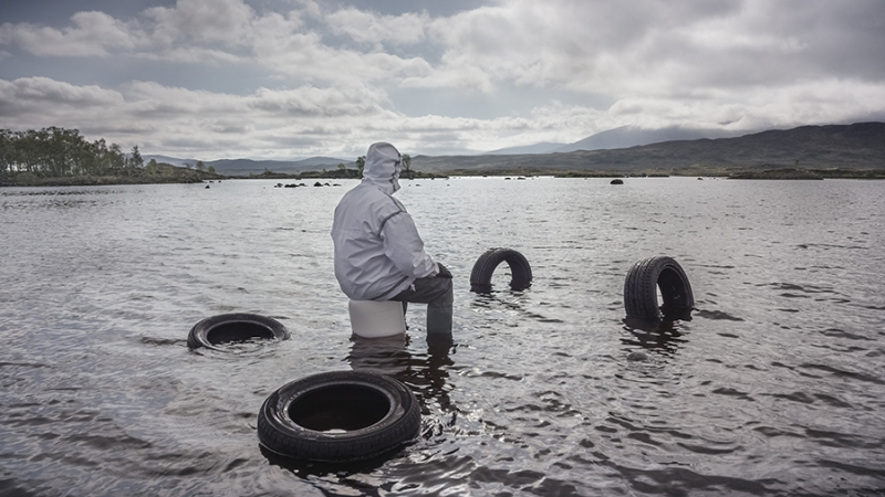 A person, dressed in rain gear, sits in a lake looking out at the horizon.
