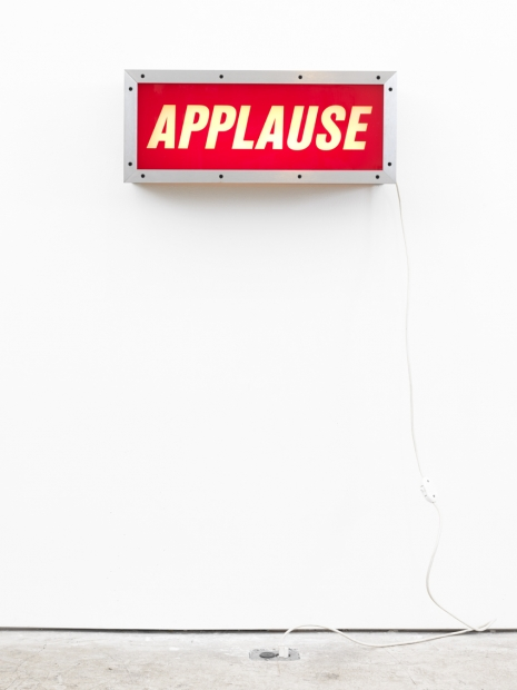 """A sculpture of a wall aluminum lightbox with the word """"APPLAUSE"""" in white slanted lettering on a red background and a white cord hanging down from the right side, mounted on a white wall."""