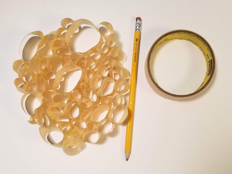 Loops of tape sticked together to form an amorphous shape, next to a number two pencil and a role of tape.