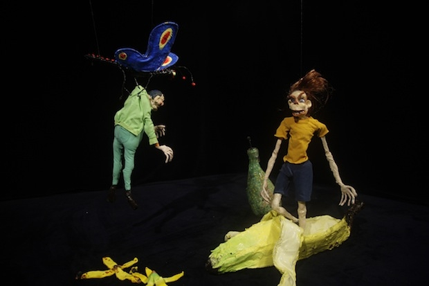 A video still of crudely-rendered clay figures caught mid-action in a dark, ambiguous space.