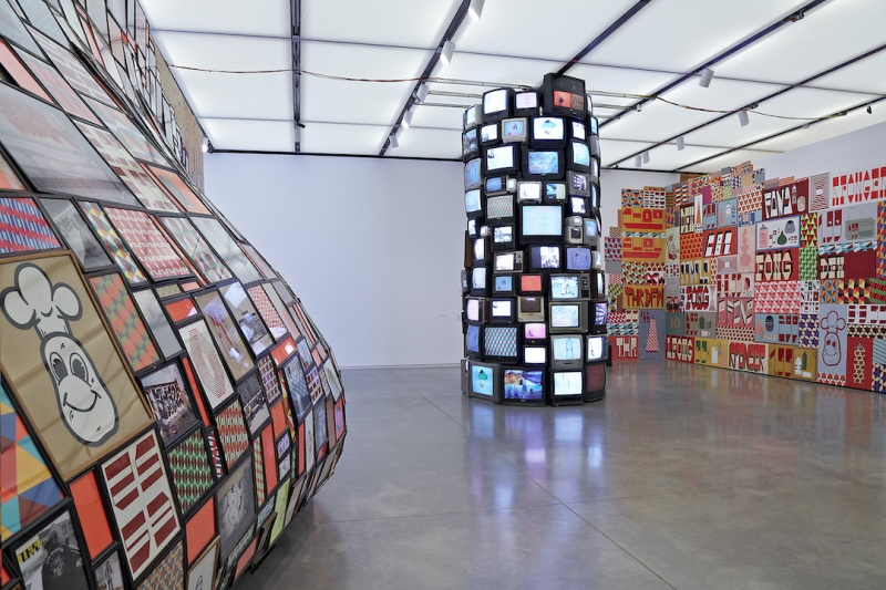 A monumental installation consisting of a towering sculpture made of television screens, a wall-sized mural, and a convex sculpture made of colorful framed graphics coming off the wall.