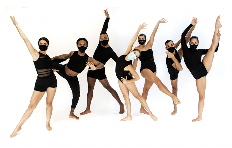 7 dancers in black leotards pose in front of a white background